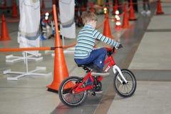 Een kleine jongen berijdt een fiets op het spoor De jongen op de fiets binnen stock afbeelding