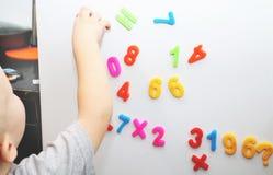 Een kleine jongen bestudeert de magnetische aantallen op de koelkast Kleuter opleiding royalty-vrije stock foto