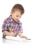 Een kleine jongen bij de lijst trekt Stock Fotografie