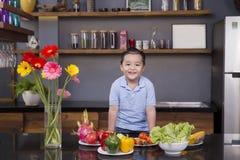 Een kleine jongen in de keuken met heel wat fruit en groente Stock Afbeelding
