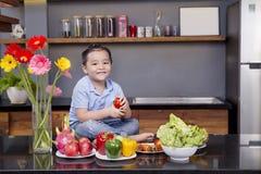 Een kleine jongen in de keuken met heel wat fruit en groente stock afbeeldingen