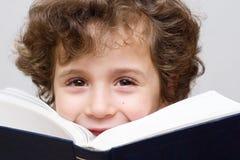 Een kleine jongen die een groot boek leest stock fotografie