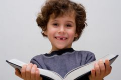 Een kleine jongen die een groot boek leest royalty-vrije stock afbeeldingen