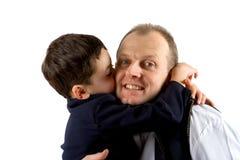 Een kleine jongen die een grote kus op de wang van zijn vader plant royalty-vrije stock afbeelding