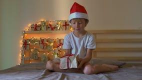 Een kleine jongen die een heden van een komstkalender openen die op een bed hangt dat met Kerstmislichten wordt verlicht stock video