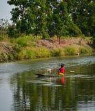 Een kleine jongen die houten boot op kanaal roeien stock foto