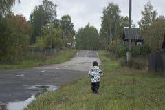 Een kleine jongen die langs de weg in een Russisch dorp gaan royalty-vrije stock fotografie