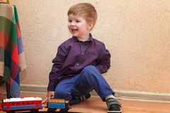 Een kleine jongen die met een spoorwegzitting spelen op de vloer stock foto