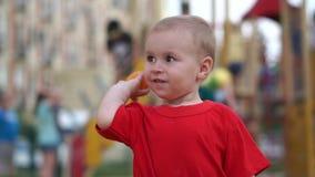 Een kleine jongen die een stuk speelgoed mandarijn proberen af te bijten en werpt het weg in langzame motie stock videobeelden