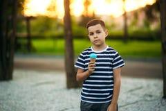 Een kleine jongen in een gestreepte T-shirt eet blauw roomijs De lente, zonnig weer Stock Foto