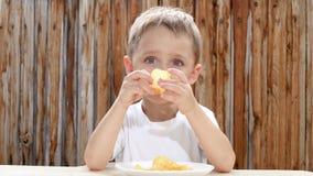 Een kleine jongen eet spaanders met genoegen Niet gezond etend kinderen Ongezond Voedsel stock video
