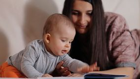 Een kleine jongen en zijn jonge moeder het letten op beelden in een boek stock footage