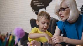 Een kleine jongen in gele t-shirt met gekleurd twee potloden zit bij de lijst en het horloge die zijn leraarstekening Tekening stock videobeelden