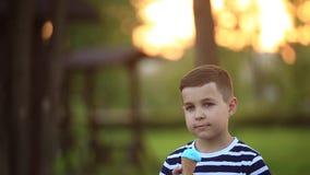 Een kleine jongen in een gestreepte T-shirt eet blauw roomijs De lente, zonnig weer stock videobeelden