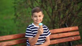 Een kleine jongen in een gestreepte T-shirt eet blauw roomijs De lente, zonnig weer stock footage