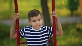 Een kleine jongen in een gestreepte T-shirt speelt op de speelplaats, Schommeling op een schommeling De lente, zonnig weer stock footage
