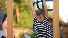 Een kleine jongen in een gestreepte T-shirt speelt op de speelplaats, Schommeling op een schommeling De lente, zonnig weer stock videobeelden