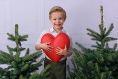 Een kleine jongen, het glimlachen, die camera, in een wit overhemd bekijken, houdt een groot, rood hart stock afbeelding