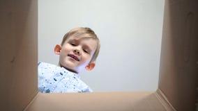 Een kleine jongen kijkt in de doos, is verrast en gelukkig om een verrassing te ontvangen Het kind opende een doos met een gift stock footage