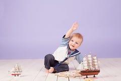 Een kleine jongen kleedde zich als zeemanskapitein van schip stock foto