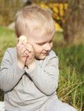 Een kleine jongen koesterde pluizige geel weinig kip met zijn han stock foto