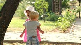 Een kleine jongen koestert een meisje in het park in de zomer stock footage