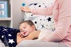 Een kleine jongen ligt in bed, doet het mamma hem een hoofdmassage Royalty-vrije Stock Fotografie