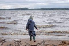 Een kleine jongen in matroos en rubberboten loopt dichtbij het meer Jongenstribunes op kust in de herfstpark, achtermening Jongen Royalty-vrije Stock Afbeeldingen