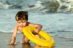 Een kleine jongen met een opblaasbare cirkel die in het overzees bespatten Stock Fotografie