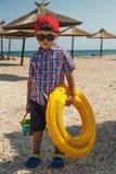 Een kleine jongen met een opblaasbare cirkel voor het zwemmen in glazen op het strand dichtbij het overzees Stock Afbeelding
