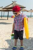 Een kleine jongen met een opblaasbare cirkel voor het zwemmen in glazen op het strand dichtbij het overzees Stock Foto's