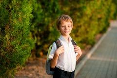 Een kleine jongen met een rugzak gaat op zijn manier naar school royalty-vrije stock foto