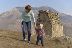 Een kleine jongen met een fopspeen reist met zijn moeder, die onder de oude Ossetian gebouwen lopen stock foto