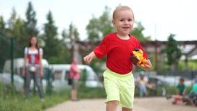 Een kleine jongen met een gebroken stuk speelgoed auto loopt gelukkig in langzame motie stock footage