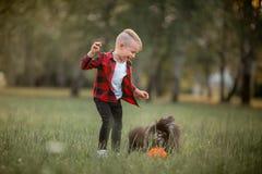 Een kleine jongen met een voetbal met zijn hond royalty-vrije stock foto's