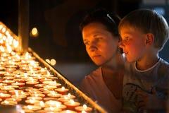 Een kleine jongen met zijn moeder zette een kaars in een heilige plaats Royalty-vrije Stock Fotografie