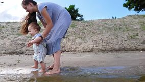 Een kleine jongen met zijn moederspelen in het water dichtbij de zandige kust stock videobeelden