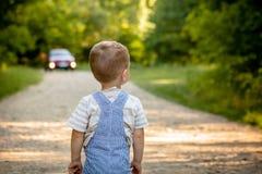 Een kleine jongen op een weg in het bosgevaar op de weg Het kind is in gevaar op de weg royalty-vrije stock fotografie