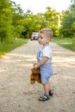 Een kleine jongen op een weg in het bosgevaar op de weg Het kind is in gevaar op de weg stock fotografie