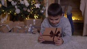 Een kleine jongen opent een doos met een gift en verheugt zich het liggen op de vloer dichtbij de Kerstboom 4K stock videobeelden