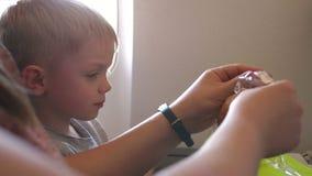 Een kleine jongen opent een zak brood op het vliegtuig, lunch op het vliegtuig stock video