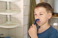 Een kleine jongen probeert te scheren en weet hoe niet stock foto
