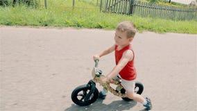 Een kleine jongen in een rode t-shirt berijdt een lopende fiets stock video