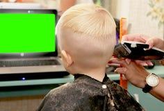 Een kleine jongen snijdt een kapper in de salon Het jonge geitje let op een beeldverhaal Het groene scherm op laptop voor handtek stock afbeelding