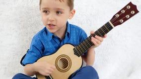 Een kleine jongen speelt een akoestische gitaar van kinderen en zingt een lied Muziek, het onderwijs van kinderen Het concept gel stock videobeelden