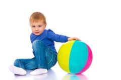 Een kleine jongen speelt met een bal Stock Foto's