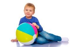 Een kleine jongen speelt met een bal Stock Afbeeldingen