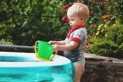 Een kleine jongen speelt met water dichtbij een opblaasbare pool De zomer en familievakantie Gelukkige kinderjaren royalty-vrije stock afbeelding