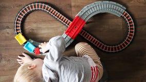 Een kleine jongen speelt een spoorweg van kinderen Het mamma let hierboven op haar zoon van Het kind wordt gefascineerd door de t stock fotografie