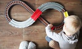 Een kleine jongen speelt een spoorweg van kinderen Het mamma let hierboven op haar zoon van Het kind wordt gefascineerd door de t royalty-vrije stock fotografie